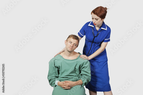 Female nurse consoling male patient against gray background