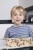 Portrait of happy young boy in front of baking tray of cookies