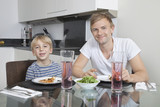 Portrait of father and son smiling at breakfast table