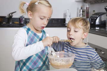 Girl baking cookie while brother tasting batter in kitchen