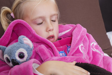 Cute little girl in pink jacket sleeping with teddy bear
