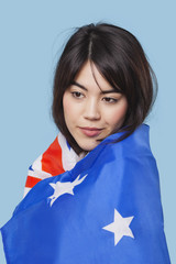 Patriotic young woman wrapped in Australian flag over blue background