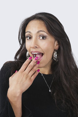 Portrait of surprised happy young woman with hand over mouth against white background