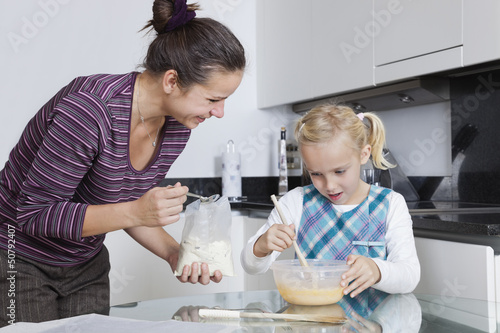Happy mother and daughter baking together in kitchen