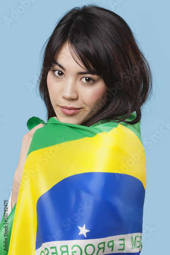 Patriotic young woman wrapped in Brazilian flag over blue background