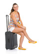 Happy young tourist woman sitting on wheel bag