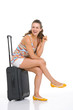 Smiling young tourist woman sitting on wheel bag