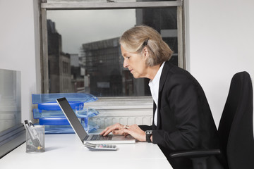 Side view of senior businesswoman using laptop at desk in office