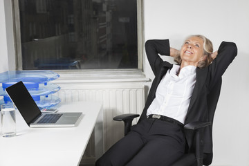 Smiling senior businesswoman relaxing at desk in office