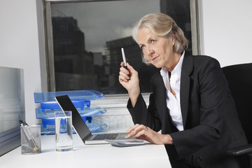 Senior businesswoman using laptop and calculator at desk in office
