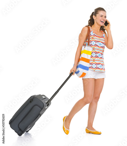 Happy tourist woman with wheel bag walking and talking mobile