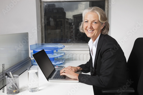 Portrait of smiling senior businesswoman using laptop at desk in office