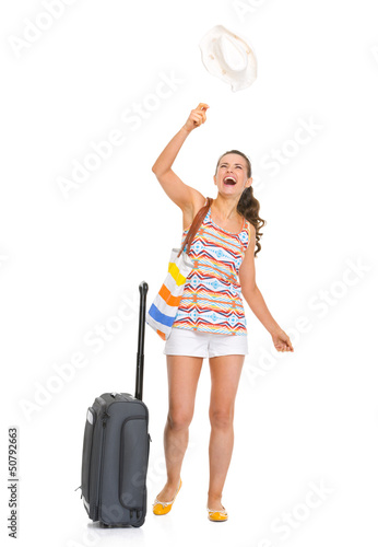Happy young tourist woman with wheel bag throws up hat