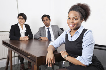 Portrait of African American female with colleagues in background at desk in office