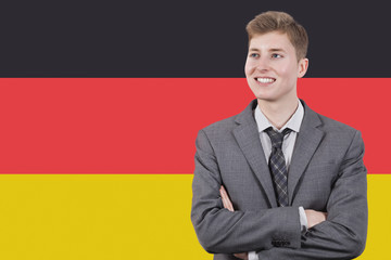 Young businessman with arms crossed over German flag