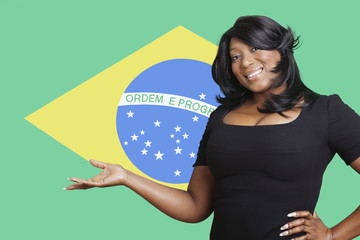 Portrait of casual mixed race woman holding out empty palm over Brazilian flag