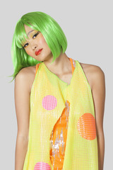 Portrait of funky young woman with green hair standing against gray background
