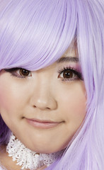 Close-up portrait of cute young woman with purple wig