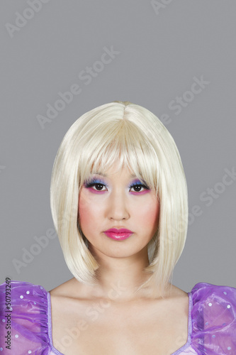 Portrait of young woman with blond hair against gray background