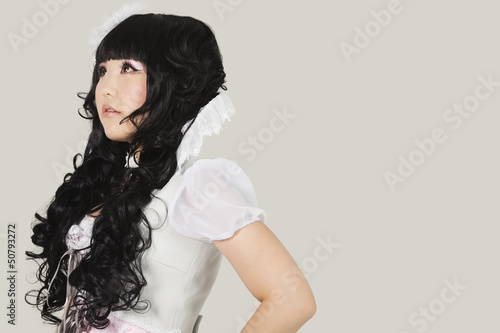 Side view of thoughtful young woman in doll costume looking away against gray background