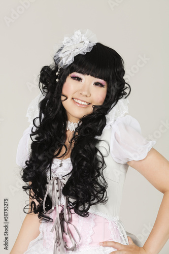 Portrait of cute happy young woman in doll costume posing over gray background