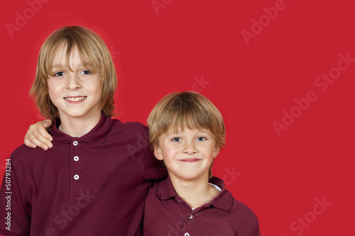 Portrait of two happy brothers against red background