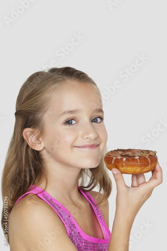 Portrait of young girl holding donut against gray background