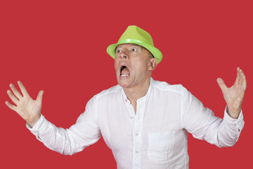 Portrait of an shocked man screaming against red background