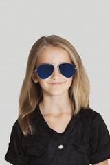 Portrait of young girl wearing sunglasses against grey background