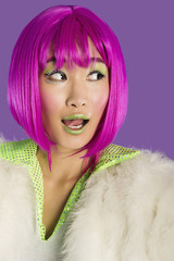 Surprised young funky woman in pink wig looking sideways over purple background