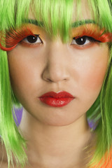 Close-up portrait of young woman wearing green wig and orange eyelashes over gray background