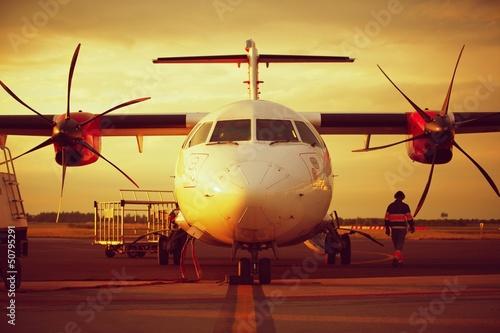 Zachód słońca na lotnisku - samolot stoi na lotnisku