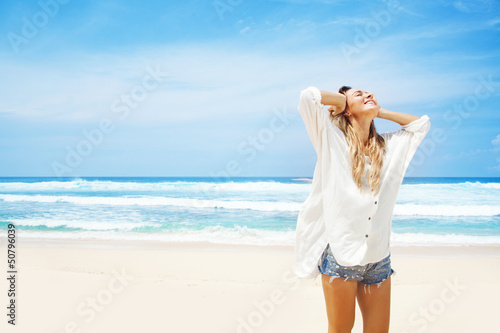 woman in white clothing refreshing at the ocean, bali - 50796039