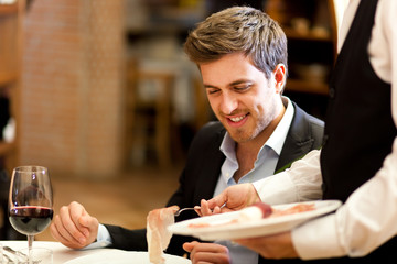Waiter serving ham to a customer