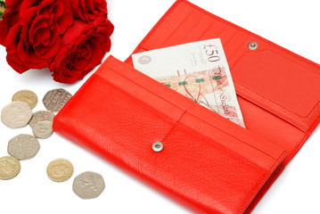 Woman red wallet, British coins, fifty pound note and roses