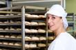 Female baker baking bread rolls