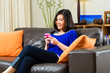 Young asian woman at home on the sofa