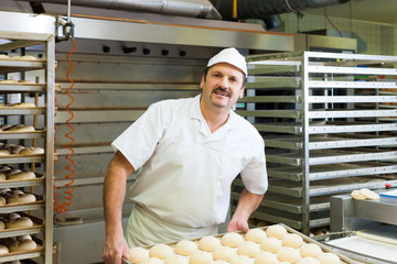 Male baker baking bread rolls