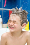 Smiling little boy covered with soap bubbles