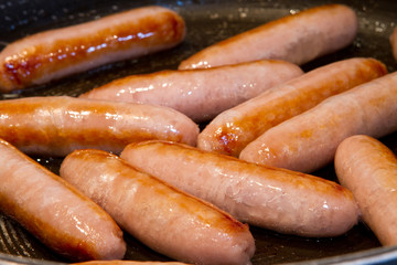 sausages frying in oil in the pan