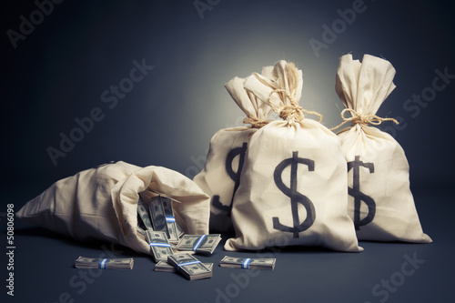 Bags full of money on a dark background