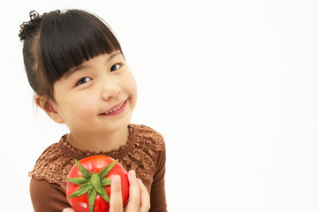 Cute asian kid with a tomato