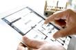 Tablet mit Rohbau und Bauplan in Händen