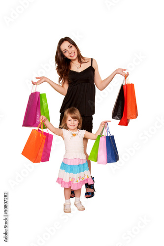 Two sisters, a teenager and a little girl holding up shopping b