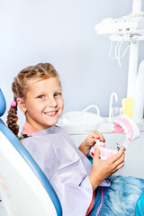 Girl cleaning toy dentures