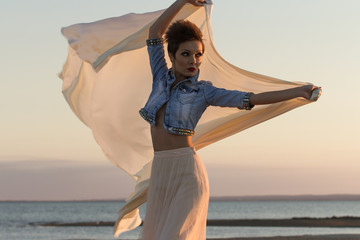 Attractive girl model posing at sunset with a cloth