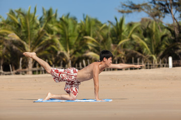 The guy of Asian appearance practices yoga on a beach