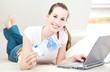 Attraktive junge Frau mit Laptop hält 20 Euro