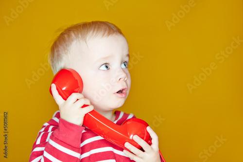 Kleines Kind hört am Telefon zu