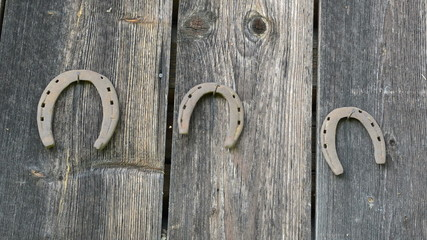 retro rusty horse shoe move hanging old wooden house wall